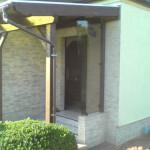 Vordach aus Massivholz mit seitlich eingefasster Glasscheibe